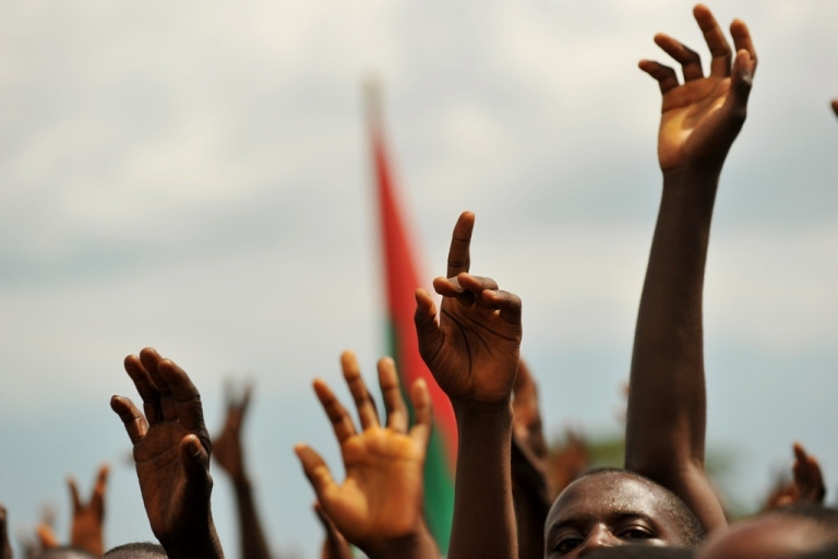<p>Supporters of Burundian President Pierre Nkurunziza raise their hands during a political rally in the town of Rugombo in northern Burundi on May 14, 2010. Does Nkurunziza really enjoy popularity with 89 percent of Burundi's people, or are they just too afraid to say?</p>