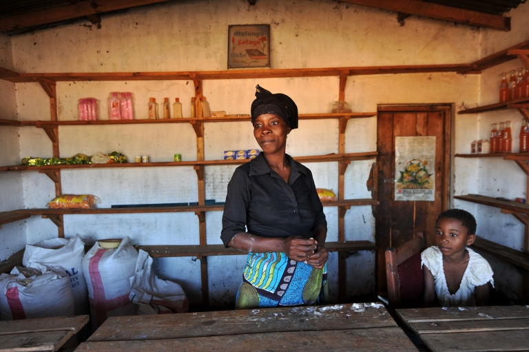 <p>Gladys Josephat, 35, poses with her children in her small shop that she got from a micro finance loan run outside Lilongwe on July 14, 2011. Malawi's microfinance lenders are giving would-be business owners access to capital in a country where 81 percent of people do not have a bank account. The system is a success for a country where frustrations at government erupted into deadly protests on July 20 and 21, leaving 19 dead in one of the world's poorest nations. AFP PHOTO /</p>