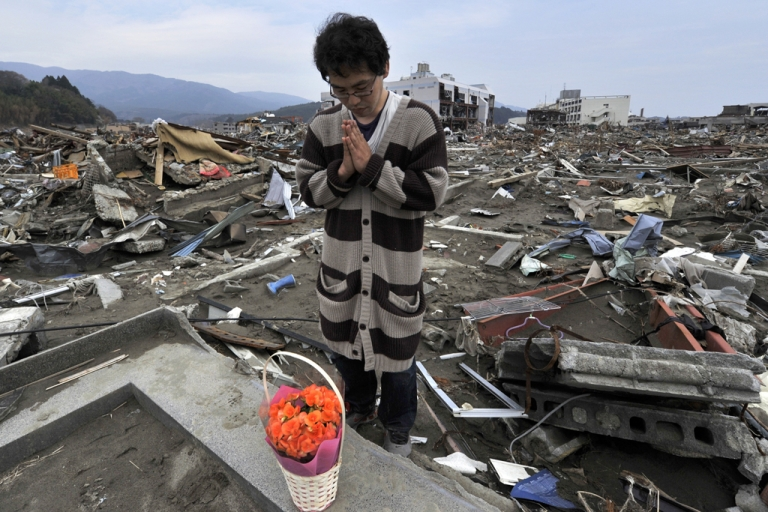 <p>Atsushi Shibata prays for his mother who died in the March 11 tsunami in the devastated town of Rikuzentakata in Iwate prefecture on May 1, 2011.</p>