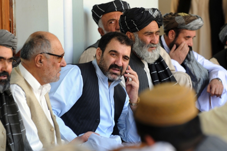 <p>Ahmed Wali Karzai (C) talks on the phone as he sits with supporters celebrating the re-election victory of his brother President Hamid Karzai in Kandahar on Nov. 3, 2009.</p>