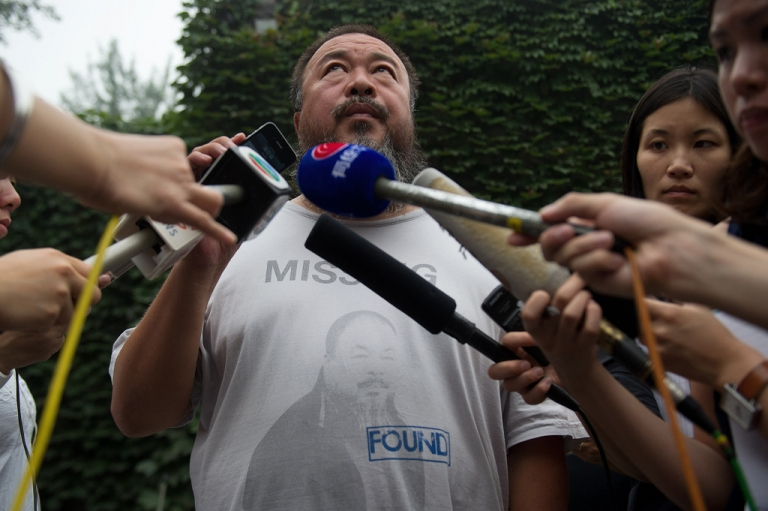 <p>Chinese artist Ai Weiwei (C) speaks to the media inside his compound in Beijing as the verdict of his court hearing is announced on July 20, 2012. Ai Weiwei lost his appeal against a multi-million-dollar tax fine on a company he founded, his lawyer said.</p>