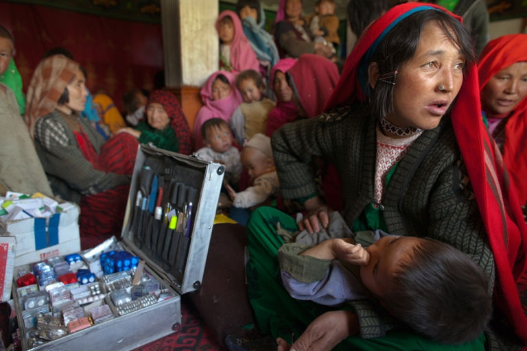 <p>Villagers wait for medical treatment in a makeshift mobile health clinic. Some aid agencies in Afghanistan are seeing their budgets slashed as the US prepares to withdraw from the region by 2014.</p>