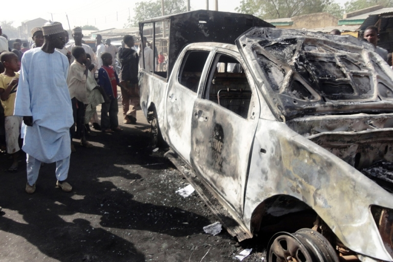 <p>A resident inspects a police patrol van that was bombed by Islamic extremists Boko Haram outside Sheka police station in northern Nigerian city of Kano on January 25, 2012.</p>