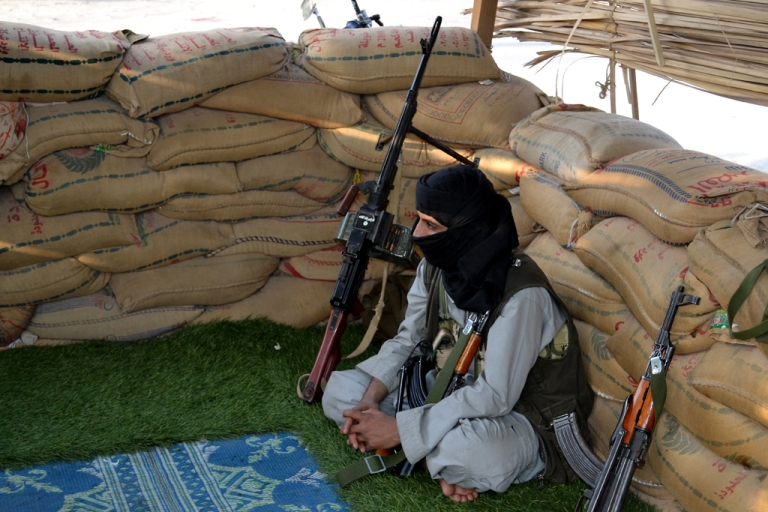 <p>A militant suspected of being a member of Al-Qaeda sits at a checkpoint in Azan in the southern Yemeni province of Shabwa.</p>