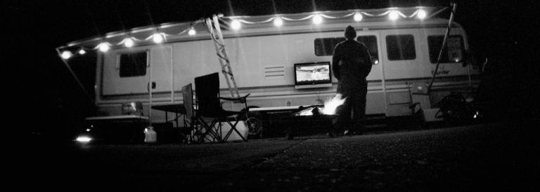 <p>A fan watches a football game in front of his RV in Talladega, Alabama. A part of the state's immigration law that would require proof of citizenship to register a mobile home was blocked by a federal judge.</p>