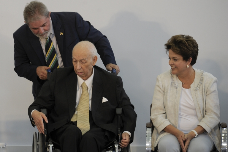 <p>Former Brazilian President Luiz Inacio Lula da Silva adjusts the wheelchair of his former Vice-President Jose Alencar as Brazil's President Dilma Rousseff watches during a ceremony on January 25, 2011.</p>
