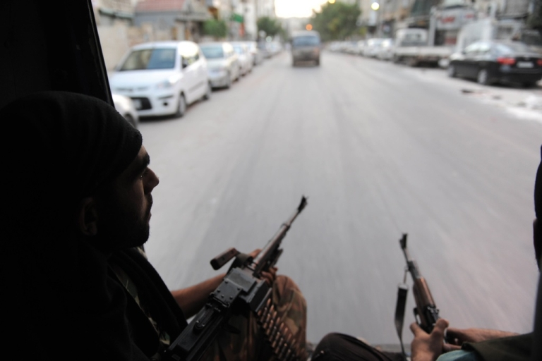 <p>Syrian rebels arrive in the city of Saladin, near Aleppo, to attack the municipal building on July 23, 2012.</p>