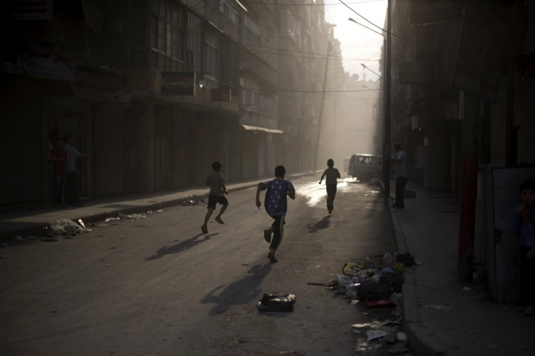 <p>Syrian boys run for cover in Aleppo on Oct. 9, 2012.</p>