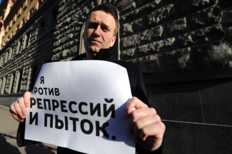 <p>Russian opposition activist and blogger Alexei Navalny holds a poster reading