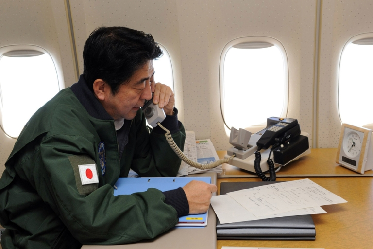 <p>Japanese Prime Minister Shinzo Abe talks on a phone at his office while in flight on a government plane heading to Jakarta from Bangkok on January 18, 2013. Abe is to cut short his visit to Indonesia, to fly home and deal with the hostage crisis in Algeria on January 19 in which numerous Japanese are caught up.  Abe is on the final leg of his first foreign trip since returning to office late last year.</p>