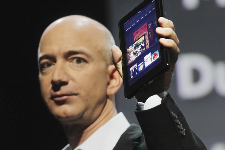 <p>Amazon founder Jeff Bezos holds the new Amazon tablet called the Kindle Fire on September 28, 2011 in New York City. The Fire, which will be priced at $199, is an expanded version of the company's Kindle e-reader that has 8GB of storage and WiFi. The Fire gives users access to streaming video, as well as e-books, apps and music, and has a Web browser. In addition to the Fire, Bezos introduced four new Kindles including a Kindle touch model.</p>