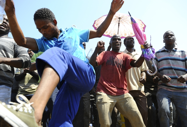 <p>Striking mine workers protest outside an Anglo American mine on October 5, 2012 in Rustenburg, South Africa.</p>