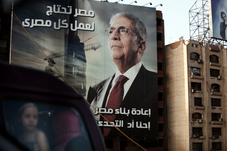 <p>A vehicle drives past a billboard in Cairo advertising former Arab League General Secretary and presidential candidate Amr Mussa on May 8, 2012.</p>