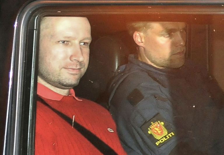 <p>Bomb and terror suspect Anders Behring Breivik (red top) leaves the courthouse in a police car in Oslo on July 25, 2011, after the hearing to decide his further detention. Breivik will be held in solitary confinement for the first four weeks, with a ban on all communication with the outside world in a bid to aid a police investigation into his acts.</p>