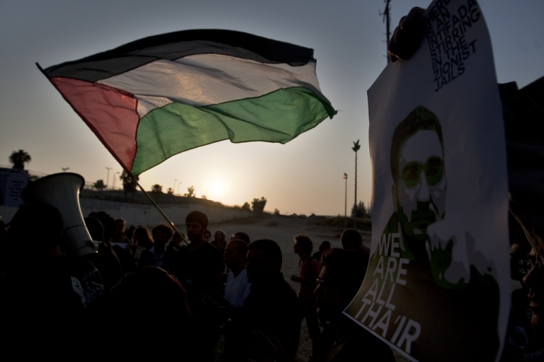 <p>Palestinian and Arab Israeli protestors wave the Palestinian flag and hold a poster picturing Thaer Halahla, who has been on hunger strike for more than 64 days, during a demonstration in solidarity with Palestinian prisoners held in Israeli jails outside the Massiyahu Prison in Ramle, near Tel Aviv, on May 3, 2012 At least 1,550 imprisoned Palestinians are now taking part in a mass hunger strike, Israel's Prison Service said on May 2.</p>