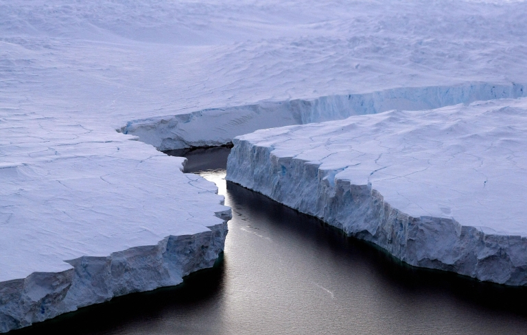 <p>An enormous iceberg (R) breaks off the Knox Coast in the Australian Antarctic Territory on January 11, 2008.</p>