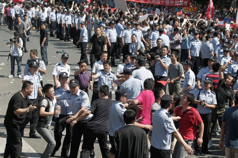 <p>Chinese policeman stops a protester from throwing an egg as he marches during an anti-Japanese protest over the Diaoyu islands issue outside the Japan Embassy on September 15, 2012 in Beijing, China.</p>