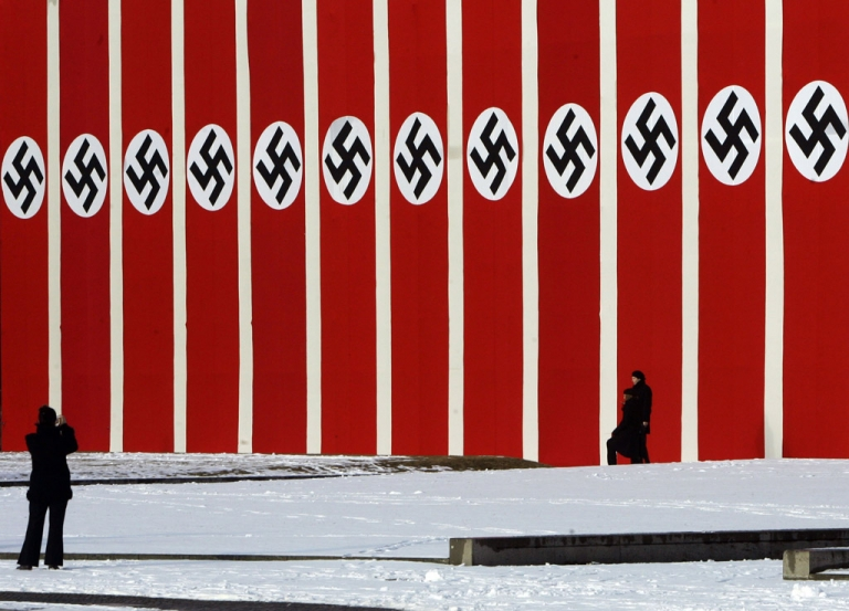 <p>People walk in front of a big wall draped with flags with Nazi symbols in Berlin's Lustgarten in front of the Old Museum. A new study has found that 20 percent of Germans still harbor latent anti-Semitism.</p>