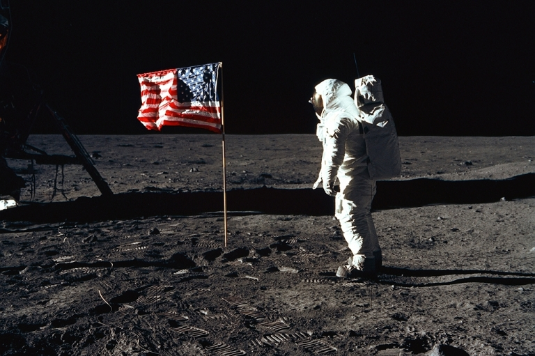 <p>Astronaut Edwin E. Aldrin, Jr., the lunar module pilot of the first lunar landing mission, stands next to a United States flag July 20, 1969 during an Apollo 11 Extravehicular Activity (EVA) on the surface of the Moon.</p>