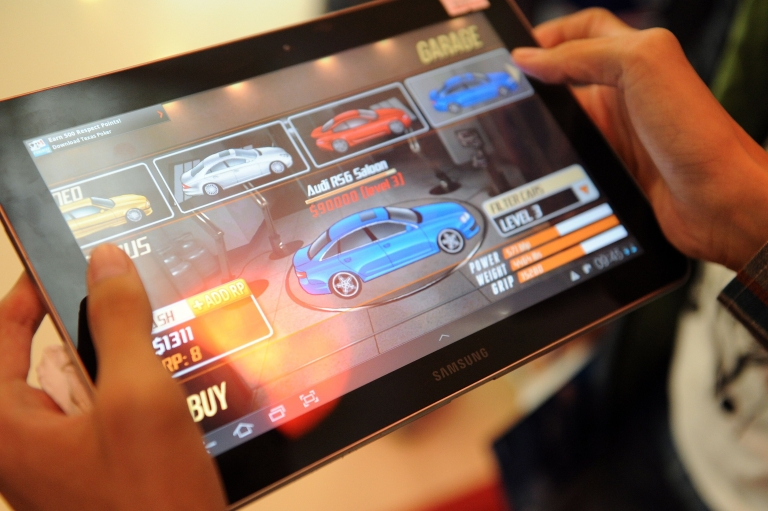 <p>A man plays a game on the Samsung galaxy tab 10.1 during a promotional sale at a shop in Phnom Penh last October.</p>