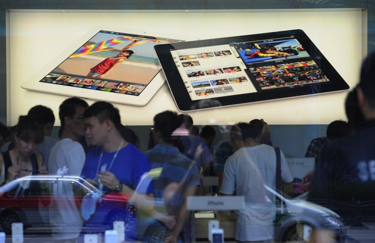 <p>Customers in Shanghai flock to an Apple store where the latest version of the Apple iPad went on sale on July 20, 2012.</p>