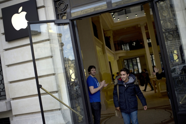 <p>A customer leaves an Apple store in Paris on September 21, 2012.</p>