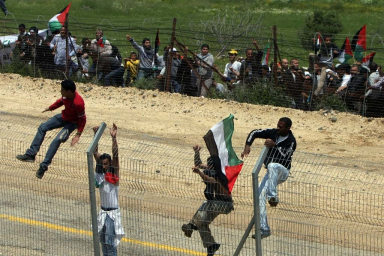 <p>Palestinian protesters infiltrate the Israel-Syria border on May 15, 2011. At least twelve people were reported killed and several injured when IDF soldiers open fired on protesters attempting to cross the Syria-Israel border. Palestinians were demonstrating the establishment of Israel in 1948, termed 'Nakba Day.'</p>