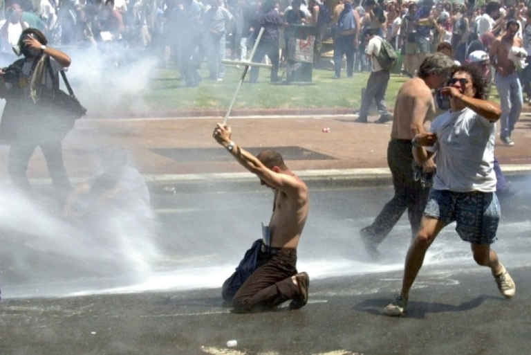 <p>An Argentine kneeling protester holds up a cross to a water cannon as police spray demonstrators Dec. 20, 2001 in the Plaza de Mayo in central Buenos Aires. Argentina plunged deep into chaos ahead of its historic 2002 default.</p>