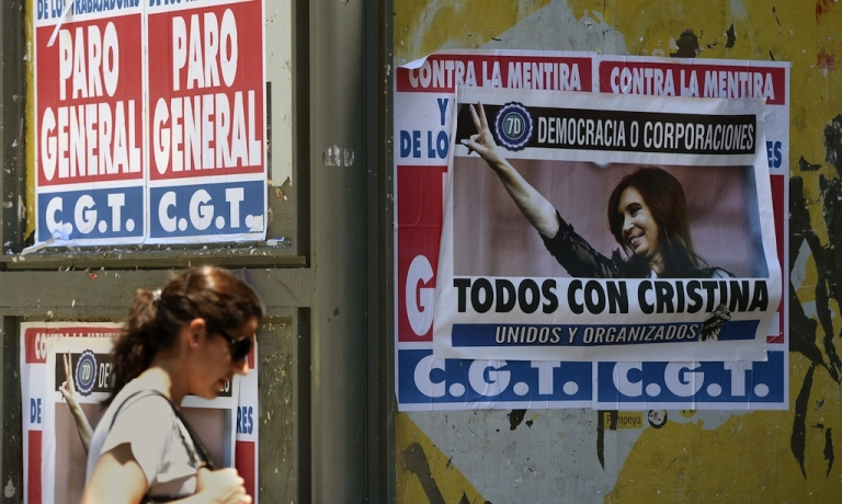 <p>A woman walks next to banners supporting and against a unions' strike that blocks the approaches to the capital, on November 20, 2012 in Buenos Aires. A general strike was called Tuesday by the working unions opposing the government of President Cristina Fernandez de Kirchner to protest against the taxes on wages.</p>