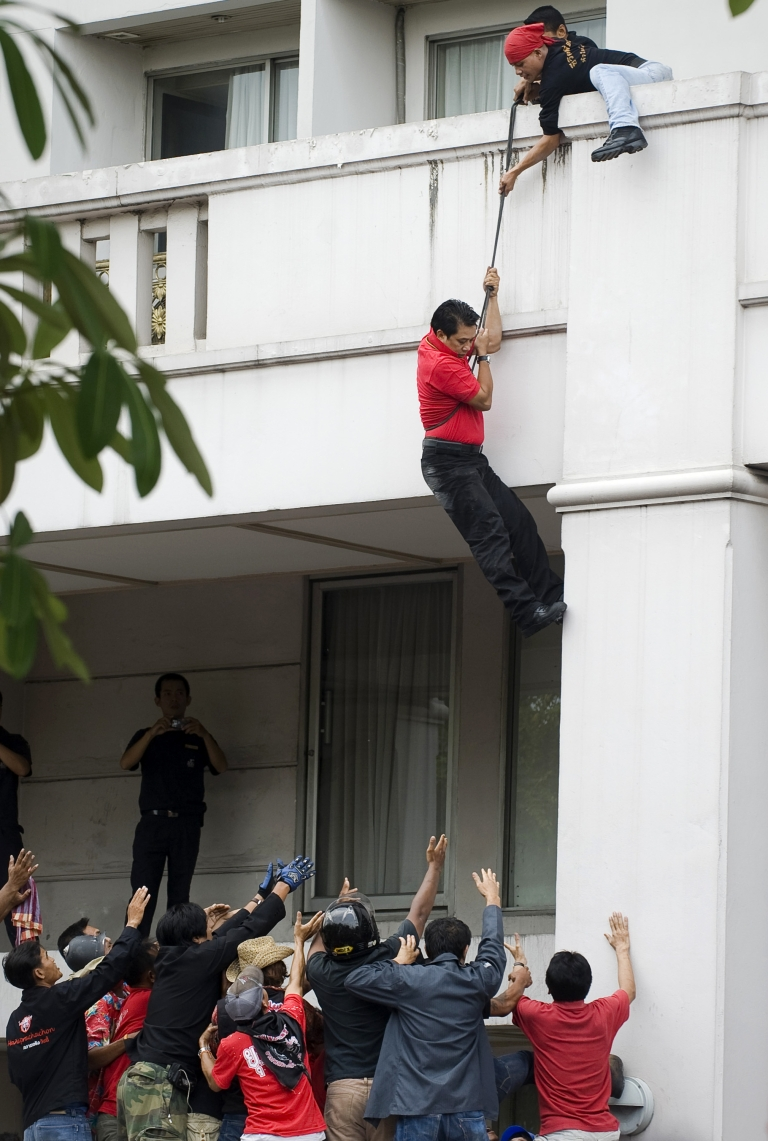 <p>'Red Shirt' anti-government leader Arisman Pongruanrong flees police on April 16, 2010, at a downtown hotel in Bangkok using a rope.</p>
