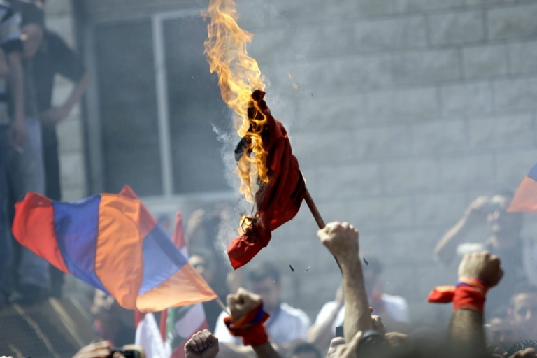 <p>Lebanese Armenians burn the Turkish flag during a protest outside the Turkish embassy in Rabieh, northeast of Beirut, to commemorate the 97th anniversary of the Ottoman Turkish genocide against the Armenian people on April 24, 2012.</p>