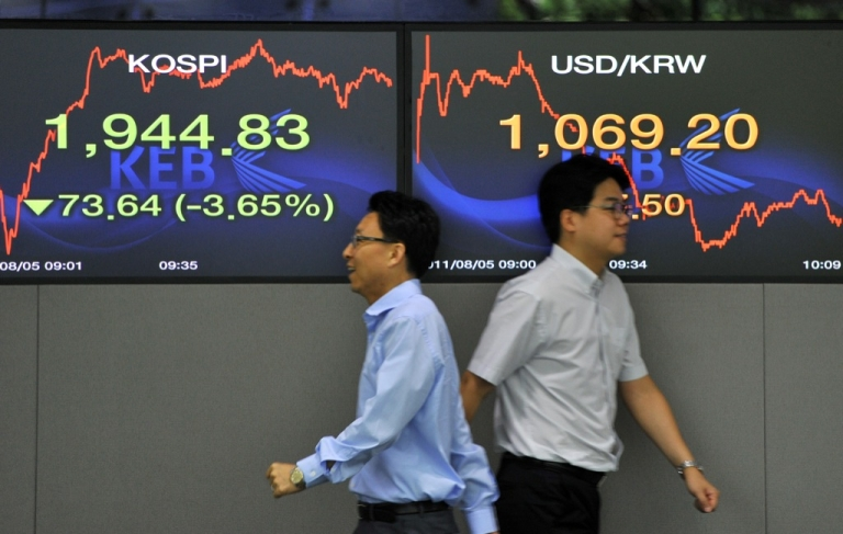 <p>Currency dealers walk past screens showing South Korea's benchmark stock index (L) and the Korean won/USD exchange rate (R) in a dealing room at the Korea Exchange Bank in Seoul on August 5, 2011.</p>