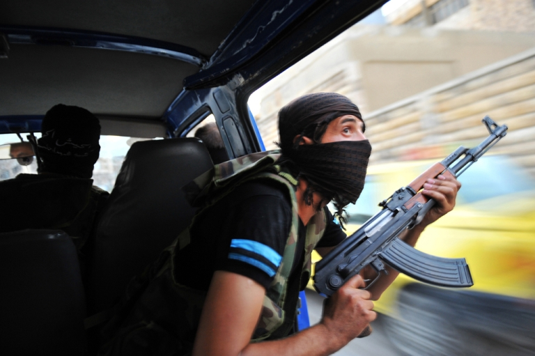 <p>Syrian rebels hunt for snipers after attacking the municipality building in the city center of Selehattin, near Aleppo, on July 23, 2012, during fights between rebels and Syrian troops. Syrian rebels