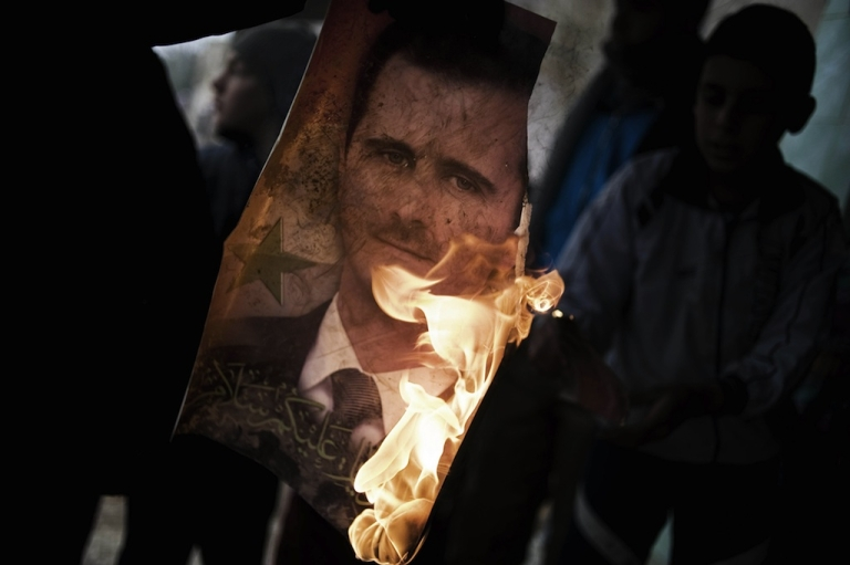 <p>A member of the Free Syrian Army holds a burning portrait of embattled President Bashar al-Assad in Al-Qsair on January 25, 2012.</p>