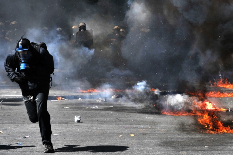 <p>A protester runs from police in Athens on Wednesday.</p>