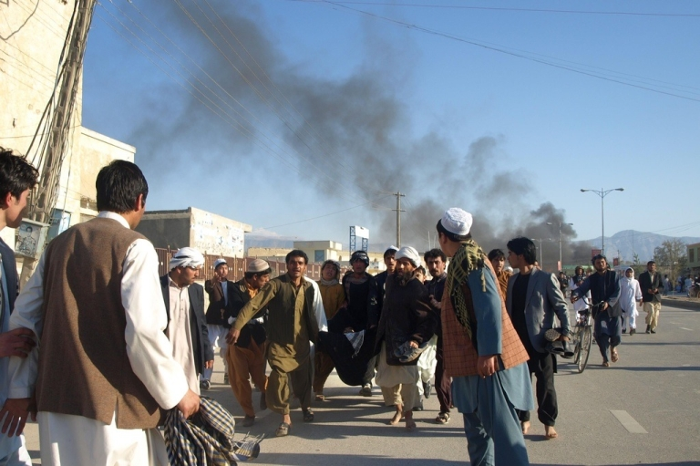<p>Smoke billows from the U.N. compound as Afghans carry a man wounded by security guards when protesters attacked the U.N. headquarters in Mazar-i-Sharif on April 1, 2011.</p>