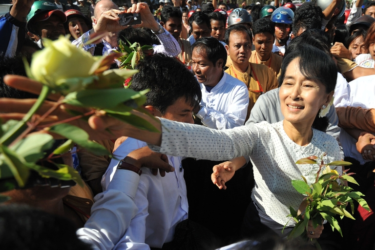 <p>Burmese opposition leader Aung San Suu Kyi is surrounded by supporters as she leaves the Thanlyin township election commission office after she registered to run as a candidate in upcoming by-elections, on the outskirts of Yangon on January 18, 2012.</p>
