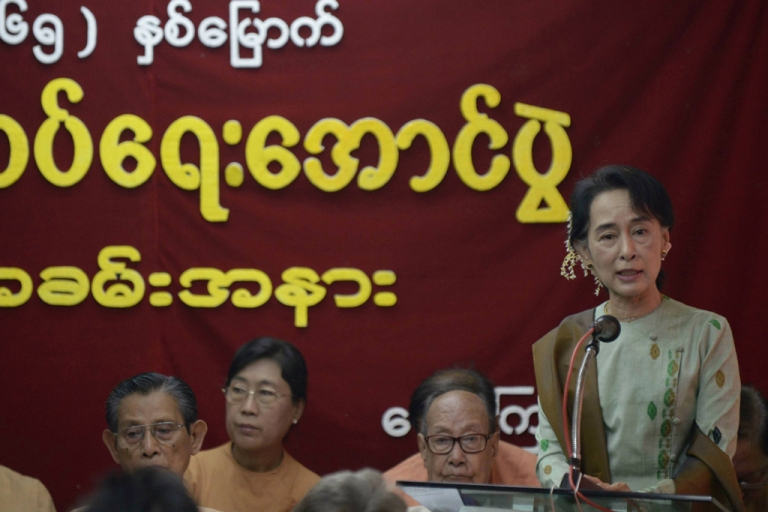 <p>Myanmar opposition leader Aung San Suu Kyi (R, standing) delivers a speech to mark the 65th anniversary of Myanmar's independence at the head office of the National League for Democracy (NLD) party in Yangon on January 4, 2013. Suu Kyi has been criticized for taking money from some of Myanmar's most notorious cronies.</p>