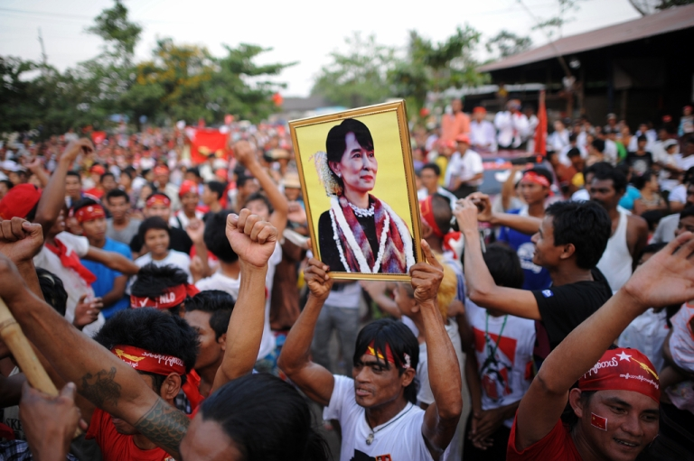 <p>A man holds a portrait of Myanmar opposition leader Aung San Suu Kyi during a rally for a candidate of her National League for Democracy (NLD) party at a Yangon constituency on March 30, 2012. Pro-democracy leader Aung San Suu Kyi said on March 30 that by-elections in Myanmar would not be