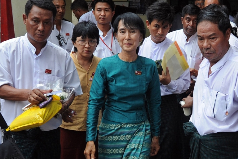 <p>Myanmar opposition leader Aung San Suu Kyi (C) walks out of her National League for Democracy (NLD) headquarters after attending a meeting of the NLD campaign committee with newly-elected NLD candidates in the April 1 by-elections in Yangon on April 7, 2012.  Suu Kyi's party won almost all the seats it contested in Myanmar elections, becoming the main opposition force in the national parliament, official results showed.</p>