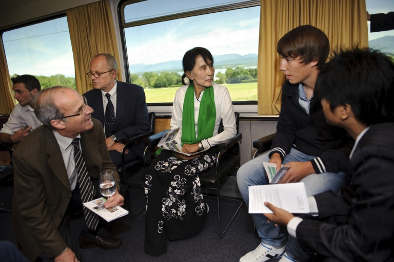 <p>Myanmar opposition leader Aung San Suu Kyi (C), speaks with Swiss apprentices on June 14, 2012 on the train between Geneva and Bern on her first trip to Europe since 1988 to formally accept the Nobel Peace Prize that thrust her into the global limelight two decades ago. Myanmar democracy icon Aung San Suu Kyi called for international investment to create jobs for her country's youth at the start of a landmark tour of Europe following years under house arrest.</p>