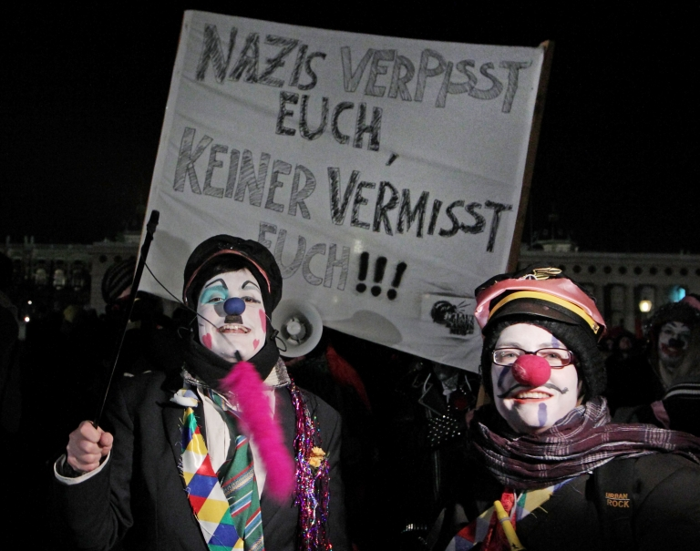 <p>Activists in clown costumes protest against the ball of far-right student organizations in the former winter imperial palace Hofburg on Friday in Vienna. Their banner reads,