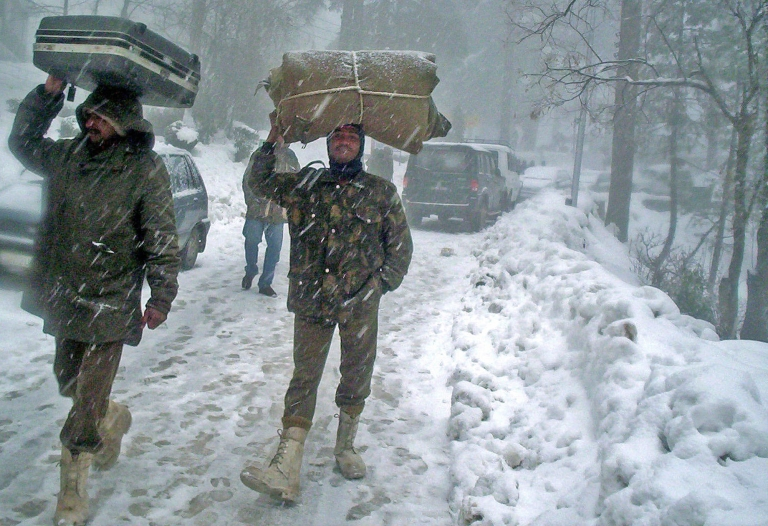 <p>Indian soldiers carry their luggage on their heads as they walk through a snowstorm on the Jammu to Srinagar Highway at Patnitop, some 110kms north of Jammu. 04 January 2006.</p>