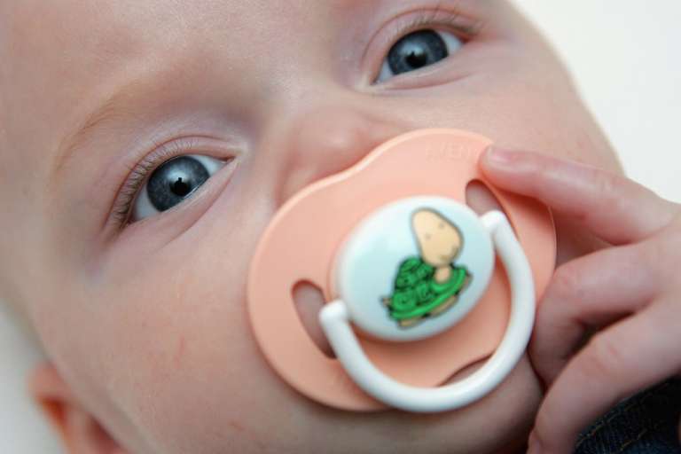 <p>A baby sucks her pacifier while laying in her crib. (Photo by Daniel Berehulak/Getty Images)</p>