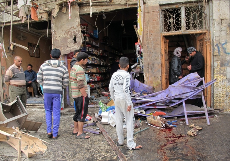 <p>Iraqis inspect the damage after a wave of attacks in Baghdad killed at least 63 people on December 22, 2011.</p>
