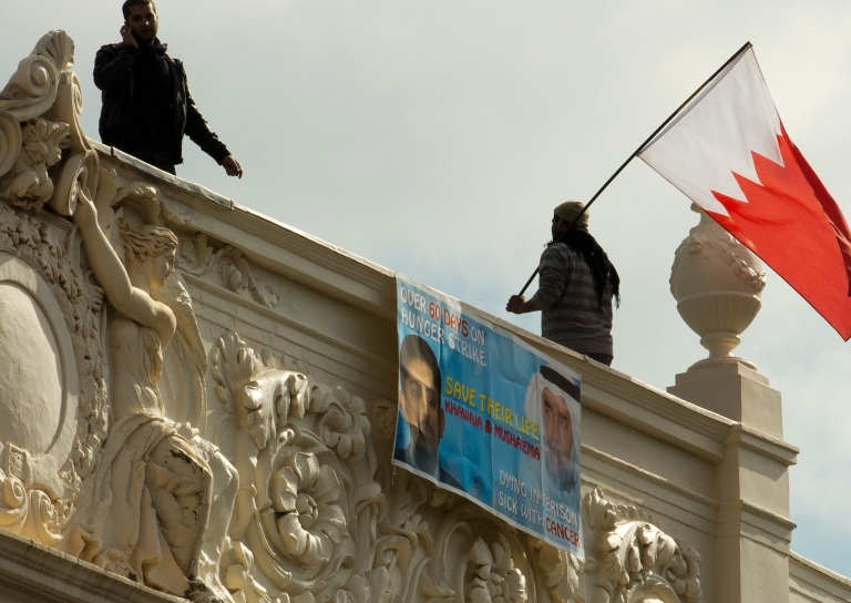 <p>A protester waves a Bahraini national flag from the top of the Bahraini Embassy in central London on April 16, 2012 during a protest over the imprisonment of political activist Abdulhadi al-Khawaja.</p>