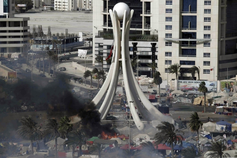 <p>Black smoke rises from burning tents as Bahraini security troops raid the one-month-old pro-democracy sit-in at Pearl Square in the capital Manama on March 16, 2011.</p>