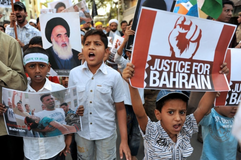<p>Young Indian Muslims pose with placards during a protest rally against the ongoing political turmoil in Bahrain on March 27, 2011.</p>
