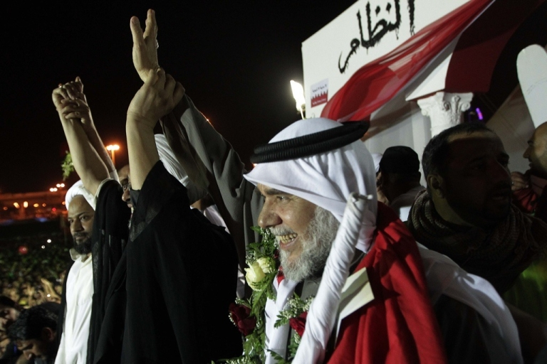 <p>Bahraini Shiite opposition leader Hassan Mashaima, left, greets anti-government protesters gathered at Pearl Square in Manama on February 26, 2011 upon his return from self-imposed exile following assurances from the Gulf kingdom that he had been pardoned of terrorism-related charges. Bahrain's protests put it at the center of the bitter divide between Sunnis and Shias in the Gulf.</p>