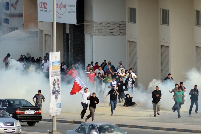 <p>Bahraini anti-government protesters run for cover from tear gas during clashes with riot police near the headquarters of the main Shiite opposition group, Al-Wefaq, in Zinj Village, west of Manama, on December 23, 2011.</p>